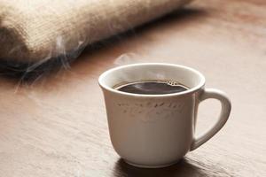 xícara branca em mesa de madeira foto