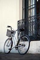 vintage kromad cykel med korg bredvid ett husfönster