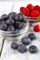 glasskålar med hallon och blåbär på träbakgrund foto