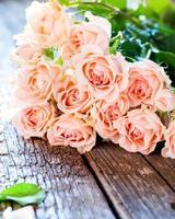 bukett med rosa rosor på träbord