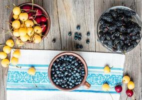 färska blåbär, körsbär och mullbär, rustik foto