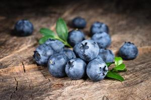 blåbär med blad på träbakgrund foto