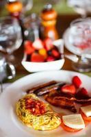 frukost med omelett, färsk frukt och kaffe foto