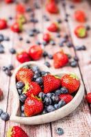 jordgubbar och blåbär i en skål på en träbakgrund foto