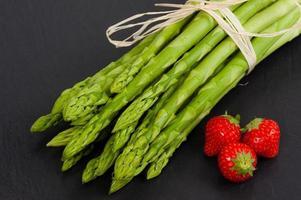 färsk grön sparris med jordgubbar foto