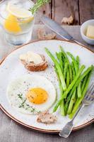 grön sparris, stekt ägg och bröd med smör. foto