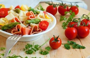 romantisk middag. läcker hjärtformad pasta med tomater, asp foto