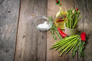 stilleben med sparris, olivolja, avokado, peppar och rosemar foto