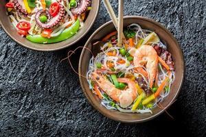 kinesiska nudlar med grönsaker och skaldjur foto