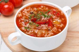 tomatsoppa med ris, grönsaker och örter, ovanifrån foto