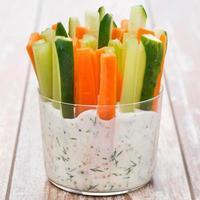 färska grönsaker i yoghurtsås på träbord foto