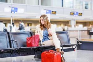 kvinna på internationell flygplats som väntar på flyg vid terminalen foto