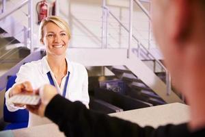 personal vid flygplatsen checkar in skrivbordet som lämnar biljett till passageraren foto