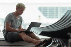 ung man använder laptop på flygplatsen foto