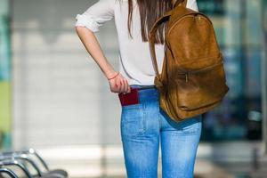 glad kvinna med flygbiljett på flygplatsen som väntar på flyg foto
