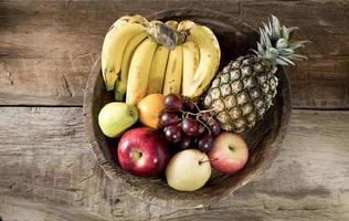 många frukt i gammalt träbricka foto