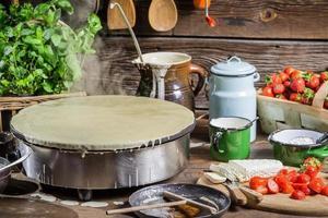 förbereder pannkakor med jordgubbar foto