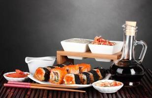 läcker sushi på tallriken, pinnar, sojasås, fisk och räkor foto