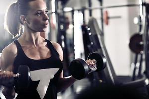 sportig attraktiv kvinna i gymmet med träningsutrustning foto