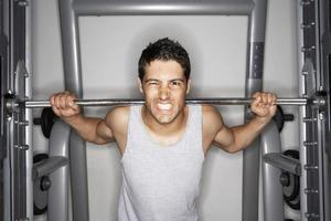 ung man lyfter vikter på gymmet foto