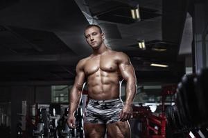 muskulös bodybuilder kille poserar i gymmet foto
