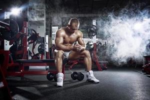 mycket kraft atletisk kille, avkopplande efter träning i gymmet