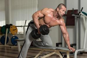 frisk man gör övning med tung vikt för ryggen foto