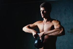 ung atletisk idrottsman som lyfter en kettlebell foto