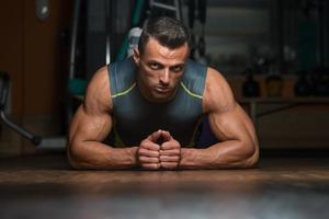 ung man gör press ups i gymmet foto
