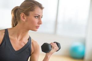 kvinna lyfta vikter på hälsoklubb foto