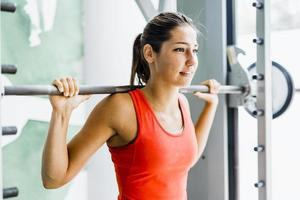 ung vacker kvinna lyfta vikter i ett gym foto