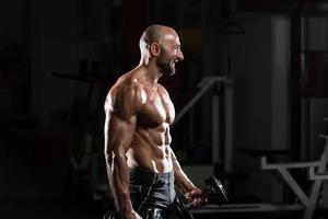 mogen kroppsbyggare som utövar biceps med hantel foto