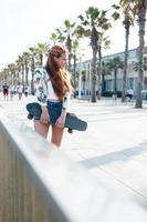 snygg kvinna skateboarder står med sitt öre styrelse utomhus