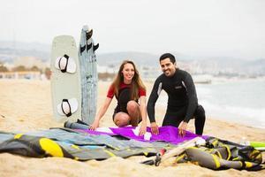 familj i våtdräkter med surfbrädor foto