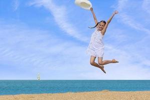 flicka hoppar över vattnet på stranden foto