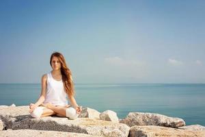 vacker ung kvinna som utövar yoga och kopplar av i lotuspose foto