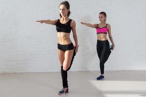 kvinnor som gör stretchövningar värmer upp stående på ett ben foto