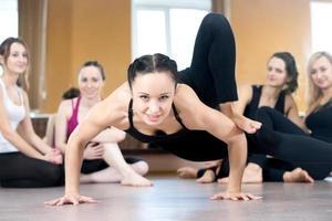 yogi tjej tränar, gör handstand armhävningar foto
