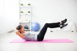 kvinna som gör bukkrossar pilates träning på matta hemma foto
