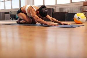 ung kvinna som gör yoga på gymmet golvet foto