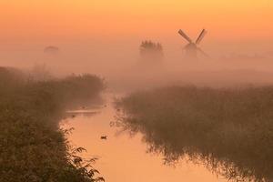 polderlandskap med historisk väderkvarn foto