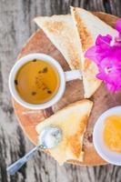 rostat bröd med ananas sylt och te. Rustik frukost foto