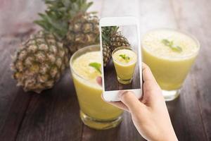 tar foto av ananassmoothien på träbord