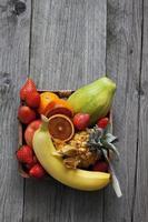 frukt skål med frukter och kniv på trä foto