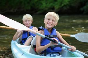 två glada pojkar som njuter av kajak på floden