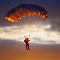fallskärmshoppare på färgglad fallskärm i solig himmel foto