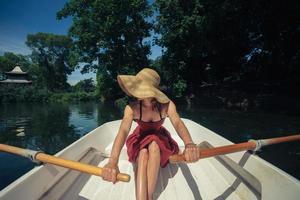 kvinna som roddar ett båt på sommaren foto