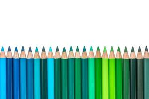 isolerad rad med blå och grönfärgade kritor foto