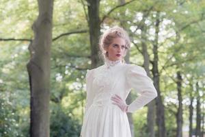retro viktoriansk kvinna framför trädrad. foto