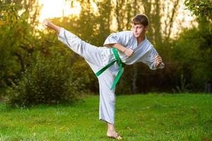 pojke i vit kimono under träning av karateövningar på sommaren foto